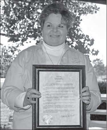 named one of the beneficiaries • Concerning the trash pick Genealogical society president Terri Gorney displays