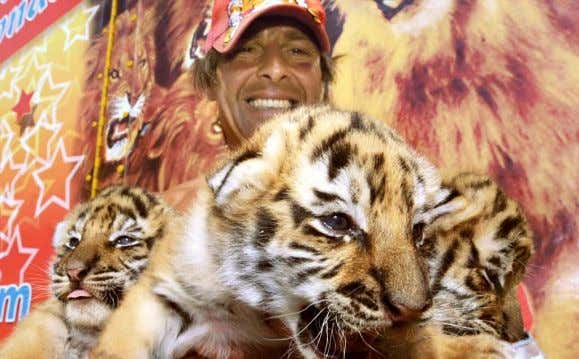 Striped Troika Circus trainer Frederic Edelstein holds three of four tiger cubs born in April at