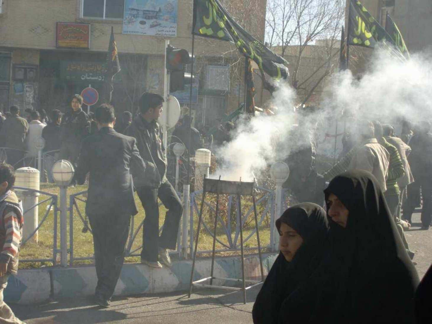 ATTENDEES BLOW ESFAND SMOKE TO PASSING-BY PARADERS OF ASHURA (ARDESTAN, IRAN)