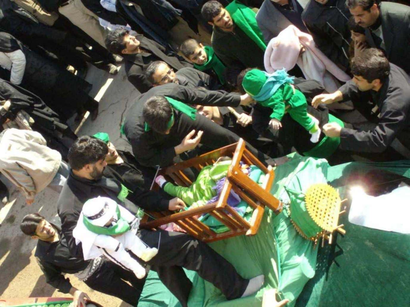 BLESSING CHILDREN DURING 'ASHURA' PARADES : Fellows attract blessing on their babies by seating them