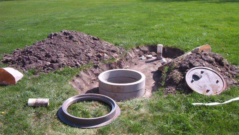 This picture shows concrete exte nsions and a manho le cover being added to a septic