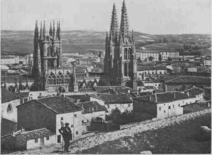 34 h1.htm THE IRON-GRAY BULK OF THE CATHEDRAL REARS ITSELF FROM CLUSTERING WALLS AND ROOFS BURGOS
