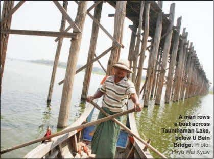 A man rows a boat across Taunthaman Lake, below U Bein Bridge. Photo: Phyo Wai Kyaw
