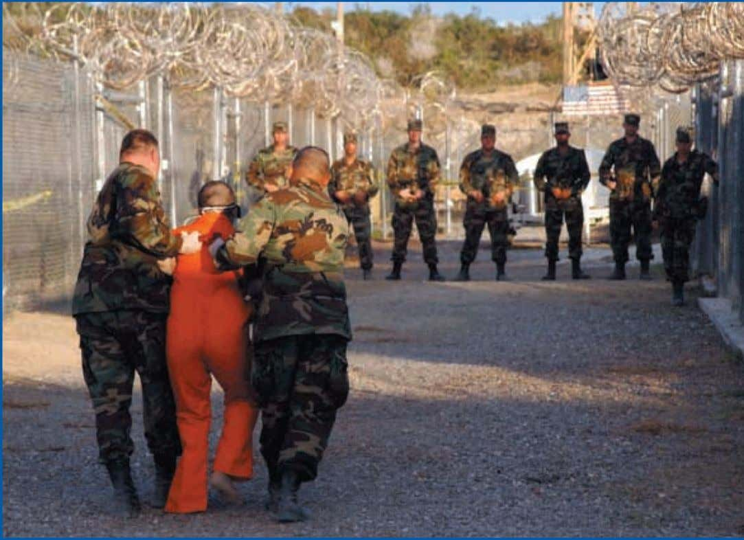 should be protected under the Ge- neva Conventions. Military police escort a prisoner to his cell