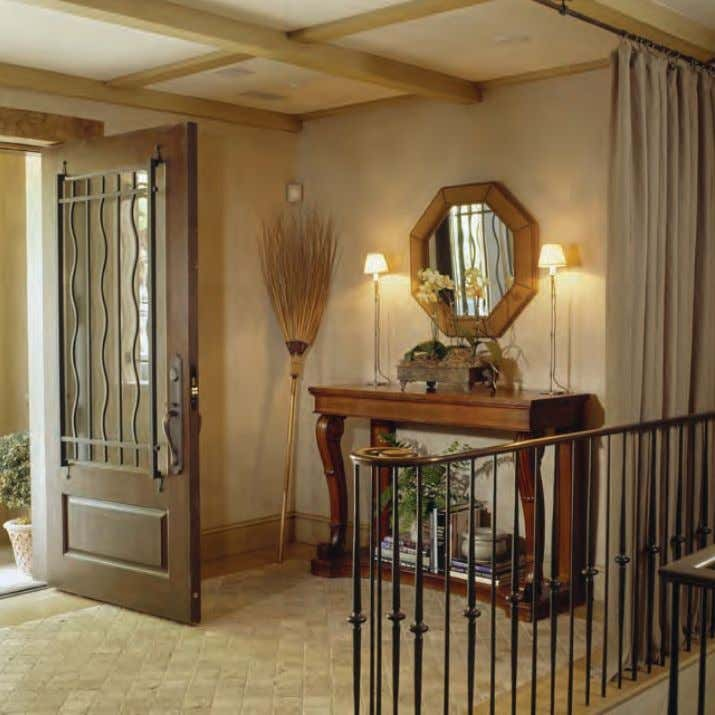 In the entrance hall, a suede and nailhead upholstered mirror hangs above a French console.