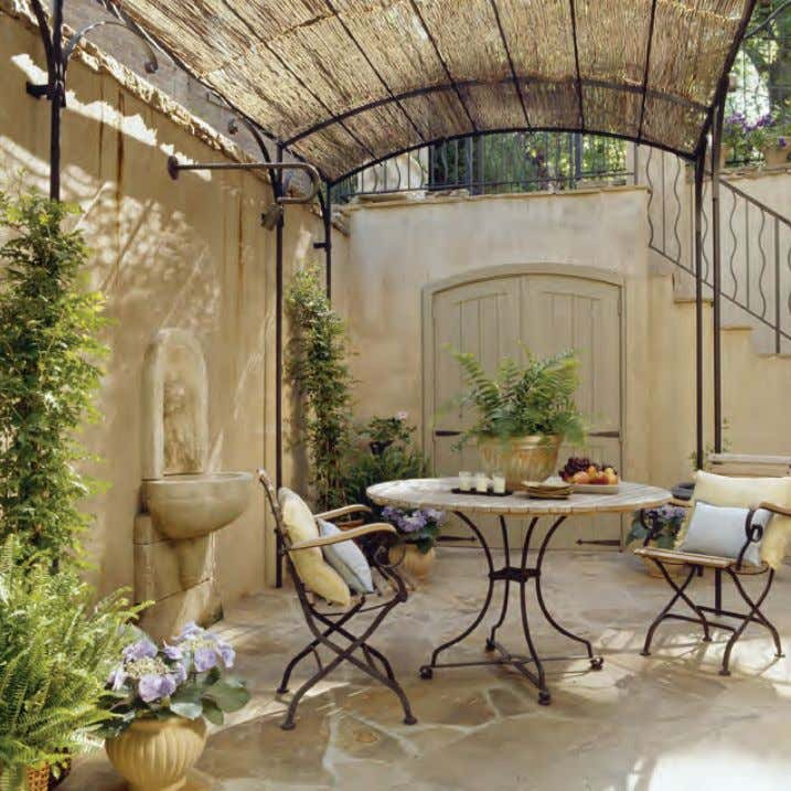 A trellis covered in willow branches provides shelter from the sun and privacy in the