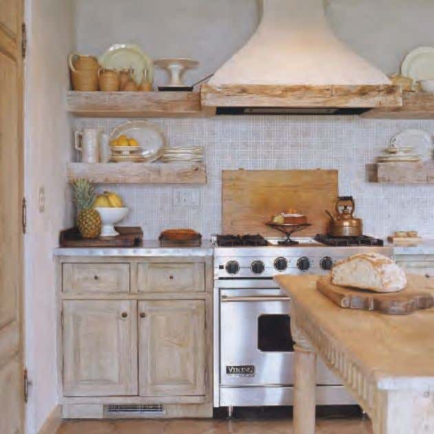 ABOVE : The kitchen has hammered zinc countertops and rough-hewn open shelves, which provide easy