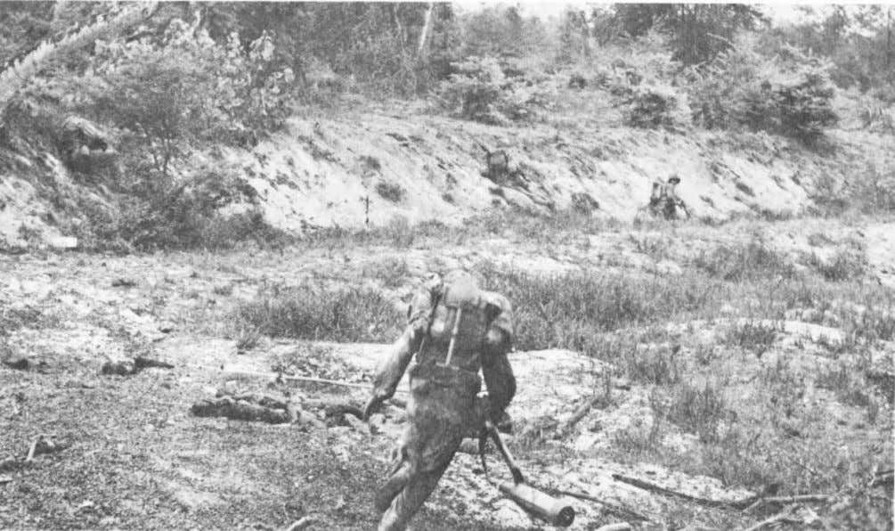 Double-timing Marine sidesteps a dead enemy soldier as he moves across an open area on