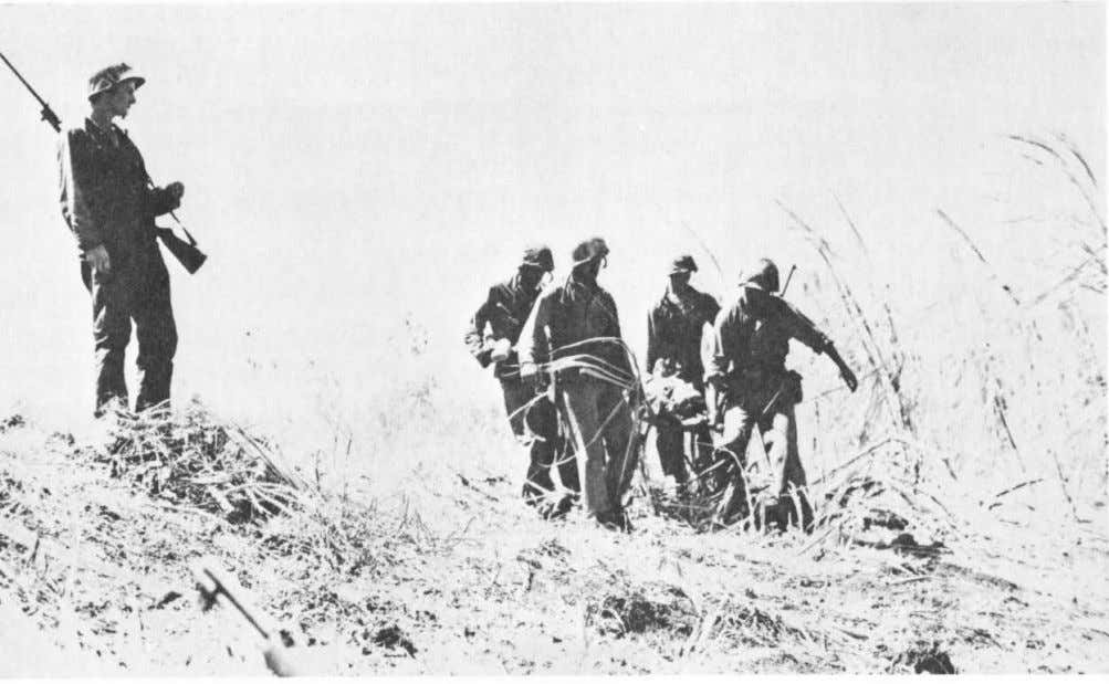 Marines on Saipan carry an injured comrade to an aid sta- tion in early June