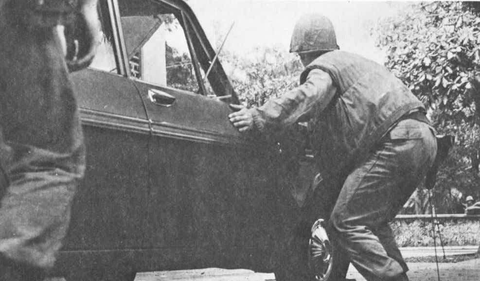 A Marine from the 1st Battalion, 8th Marines takes cover behind a car as a