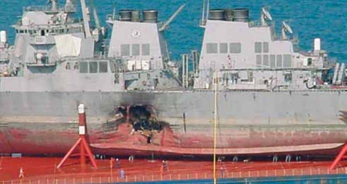 The hull damage caused by the terrorist attack on the USS Cole. hind his organization's