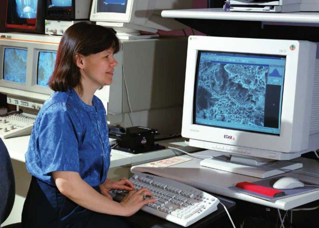 Karen Taminger analyzes an aluminum fractured surface using an electronic scanning microscope. Jeffrey Hinkley, left,