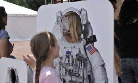 A visitor pictures herself as a NASA astronaut at the NASA booth during the Godspeed