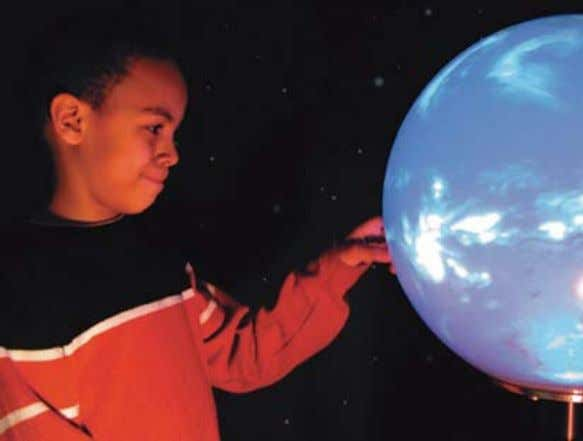 of Technol- ogy, talks to students about the Mars exhibit. A young visitor explores the center's