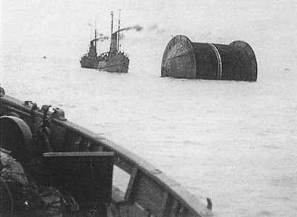 Figure 1.1 Floating Reel Towed by Allied War Ship [21] The laying of the pipe went