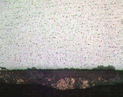 Photomicrograph of copper corrosion products dispersed throughout iron oxide matrix at ID surface.