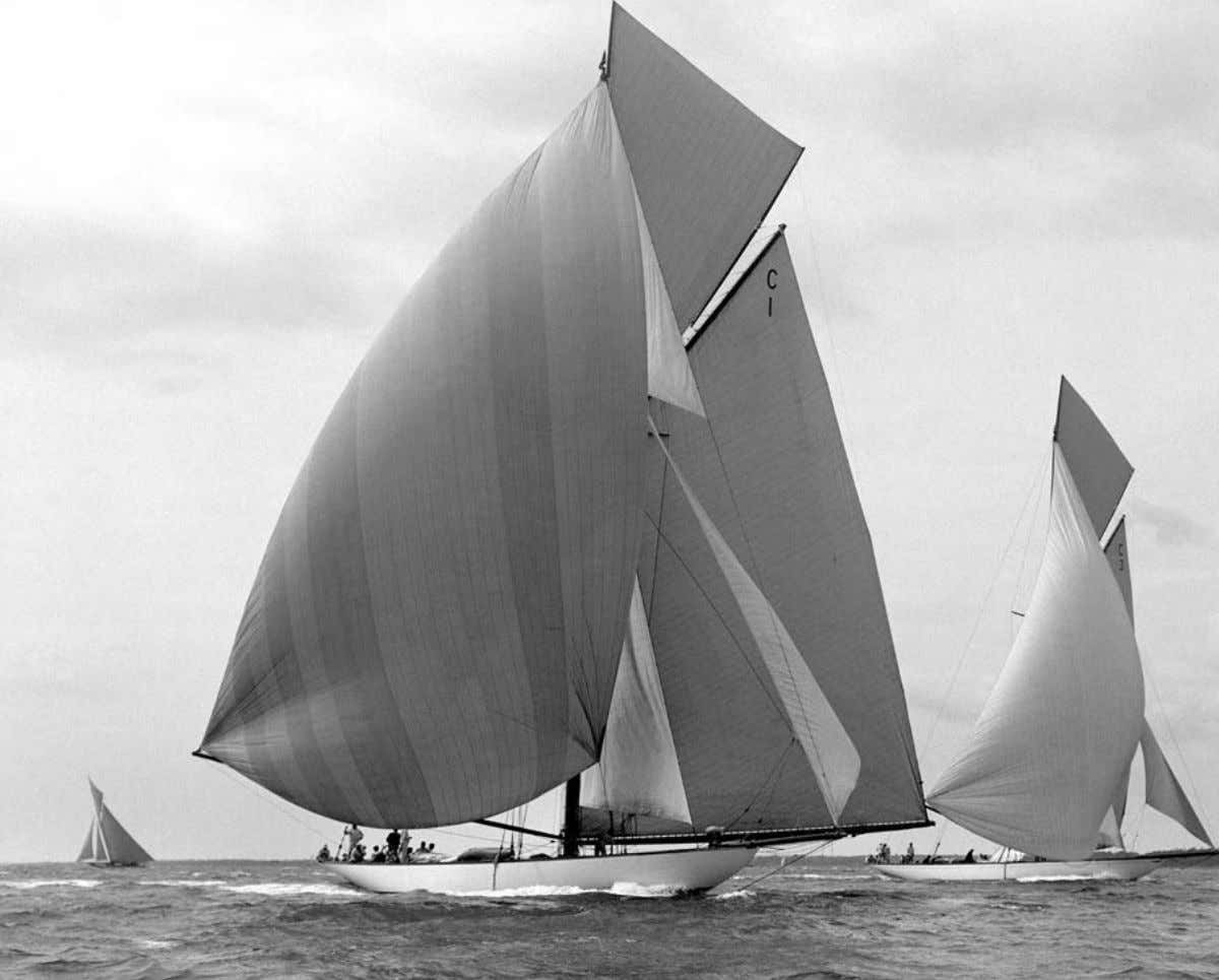 Above: Mariquita (in the foreground) racing Corona , 1912 Right: John Caulcutt helming in Cannes