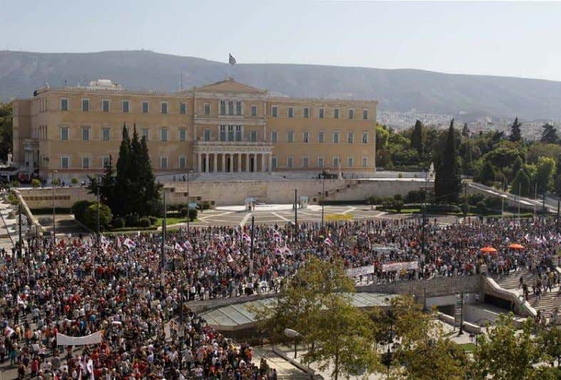 new wave of wage and pension cuts. REUTERS/Yorgos Karahalis Union workers gather outside the Greek parliament