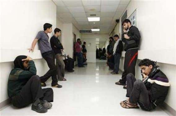 "in a planned ""Day of Rage"" that police quickly quashed. People wait at the Salmaniya hospital"