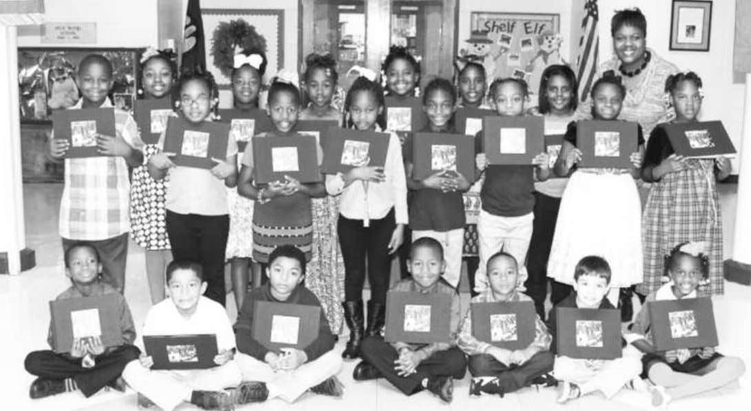 Dr. Shondra James' Donaldsonville Primary 2nd grade class proudly holds up their books. EATEL's Eighth