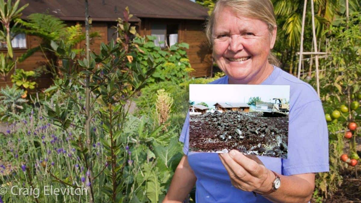 will help determine where windbreaks should be planted. Margaret holds up a photograph of her backyard