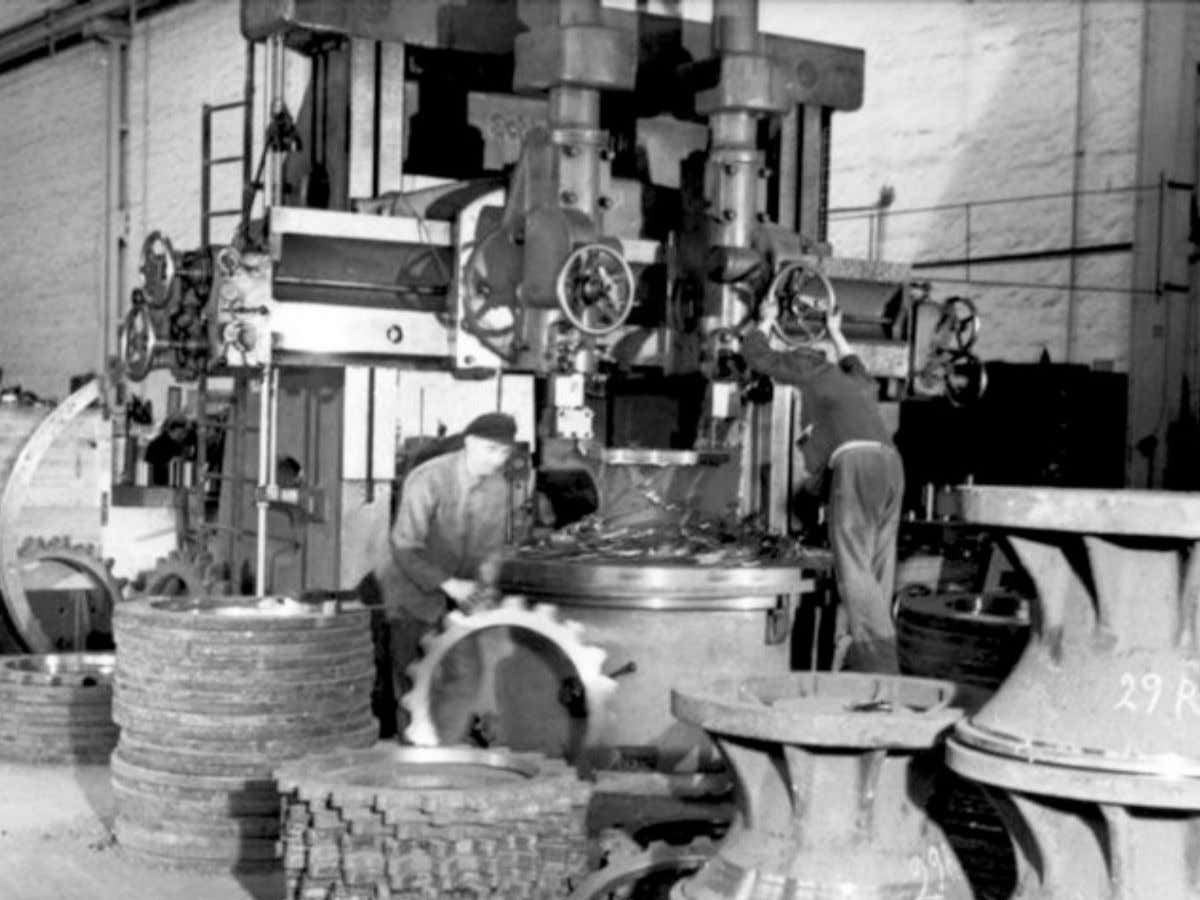 Note the large vertical lathe being used to manufacture both drive sprockets and their hubs.