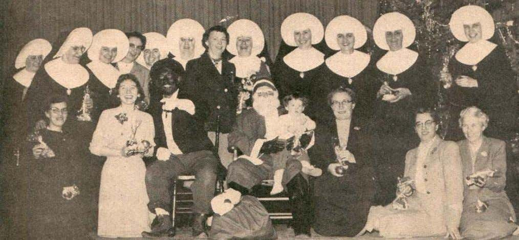 Members of the staff of St. Francis Xavier School gather for a Christmas party picture in