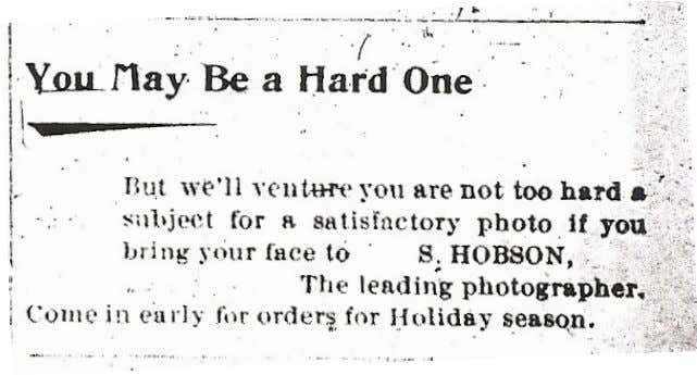humorous approach, as shown in his 1899 advertisement below. A photo tent appears behind a dwelling