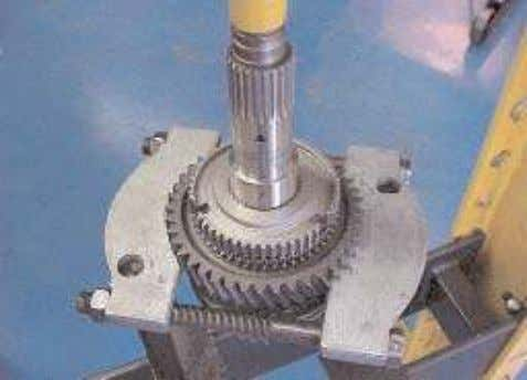 Remove the reverse/low synchroniser hub retaining snap ring. 10. Assemble puller plates under the low gear