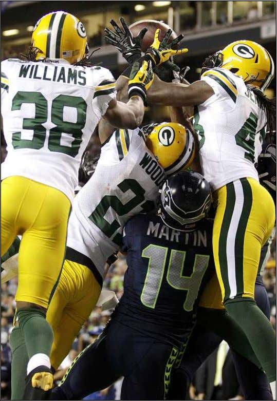 NATIONAL FOOTBALL LEAGUE AP PHOTO Green Bay defenders fight for possession with Seattle wide receivers Charly